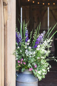 A vintage milk can overflowing with a gorgeous arrangement of greenery and delicate white and purple flowers welcomes guests to a rustic chic wedding reception at the Historic Barns of Nipmoose. Chelsea Proulx Photography, Samantha Nass Floral Design