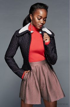 "Aja Naomi King of ""How to Get Away With Murder"" wears a red turtleneck, tweed jacket, and high-waisted jacquard shorts"