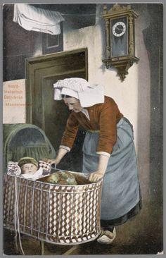 Vrouw in Noord-Brabantse streekdracht bij een wieg met baby. Aan de wand hangt een klok. voor 1905 #NoordBrabant