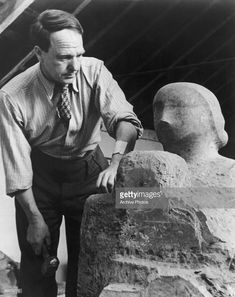 English artist Henry Moore (1898 - 1986) at work on 'Madonna and Child', 1943. The sculpture was commissioned for the 50th anniversary of St Matthew's Church in Northampton.