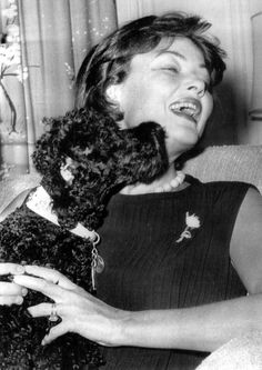 Gene Tierney, during the time of her return to the big screen in Advise & Consent, takes a licking from her poodle.