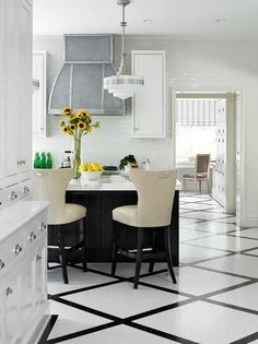 Gorgeous kitchen features a pair of schoolhouse pendants illuminating a black…