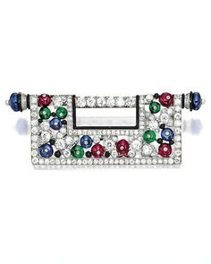 ART DECO GEM-SET, ENAMEL AND DIAMOND BROOCH, CIRCA 1920 The symmetrical plaque composed of ruby, emerald and sapphire beads, decorated throughout by old-cut diamonds and enhanced by a black enamel rim, flanked on each side with a seed pearl, the diamonds and coloured gemstones together weighing approximately 5.00 and 6.80 carats respectively, mounted in platinum.