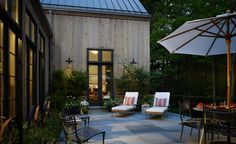Farmhouse, Soucie Horner, Ltd. / Fab exterior with the vertical board siding, the tall doors with transoms that accentuate the vertical surfaces, the large, expansive slate tiles spread across the patio, and the metal roof. Divine!