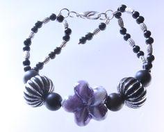 Armband , schwarze Perlmuttperlen, Metallperlen und Acrylperlen mit einer Blume aus Glas € 9.90