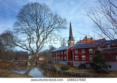 Vasteras, Sweden - 8 April, 2018: Beautiful tree in early spring on shore of Black river with swedish style houses and Vasteras Cathedral, Idyllic nordic cityscape