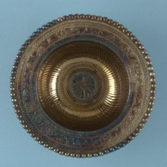 Silver flanged bowl; beaded rim; flange ornamented with foliage design in relief, including three birds and two rabbits; interior fluted, central medallion with lobed pattern.  Romano-British - 4thC