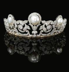 PEARL AND DIAMOND TIARA, CHAUMET, 1920 Designed as a graduated series of foliate scrolls set with rose, single, circular-cut and cushion-shaped diamonds, highlighted in the centre with a baroque button-shaped natural pear weighing 75.84 carats, (303.37 grains) and two button-shaped natural pearls, fitted case stamped Chaumet Paris 12 Place Vendôme, Londres, 22 Bruton Street.