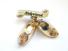 Vintage souvenir hatpins - such as this gold wood shoes brooch - make excellent gifts! This particular brooch is a travel souvenir from Helgoland, is a small archipelago in the North Sea which belongs to Germany. Its where Germans come to experience the sea, sand, boats and - with luck - sunshine. It consists of two golden shoes, similar to the French sabot or the wooden shoes sometimes associated with the Netherlands - each with a carved windmill.