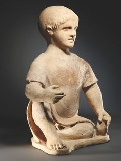 A seated boy with a dove: H. 48 cm. Grey-yellow clay with black inclusions.  Etruscan, 3rd cent. B.C.