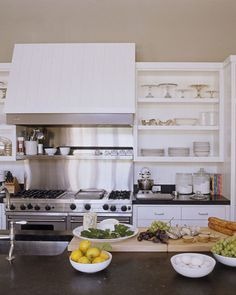 Open shelves are stocked with a collection of cake stands and hotel silver. Viking range and hood; Sub-Zero refrigerator; Bosch dishwasher; KitchenAid mixer.   - HouseBeautiful.com