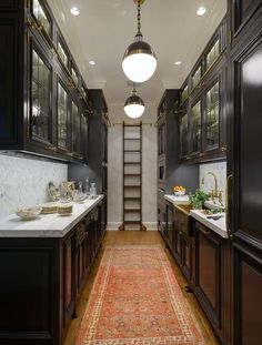 Black galley style kitchen features a row of Hicks Pendants illuminating glass front upper cabinets fitted with brass ladder rails and black lower cabinets adorned with brass hardware paired with gray and white marble countertops and backsplash.