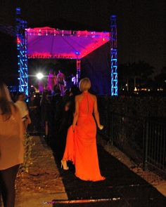 A #model prepares #backstage at LIVE: ON THE GREEN #Fashion Show #CadillacChamp #orange #gowns
