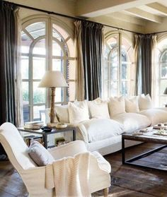 46 gorgeous living rooms to inspire you: White overstuffed slipcovered sofa white slipcovered side chair bare floors neutral palette
