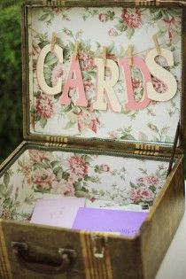 LOVE THIS :)...  Some old suitcase to collect your cards w/ some fabric glued inside to make it pretty & a ribbon draped across to hold letters spelling cards.  You could punch these letters out at work.  I'll look for grama's old suit case...Ralph may have a cuter one too.