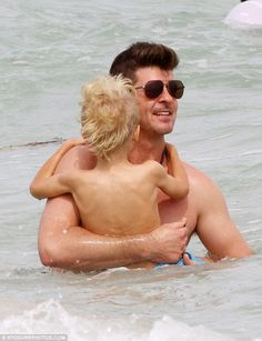 Clinging on: The star was every inch the doting dad as he paddled around with Julian in the shallows