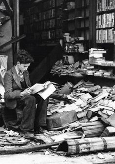 Un joven  lee sentado entre las ruinas de una librería bombardeada. Segunda Guerra Mundial. Londres, 1940.