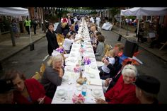 Residents sit on a long table as they take part in a street party organized by residents of Battersea in South London as Britain celebrates Queen Elizabeth II's Diamond Jubilee