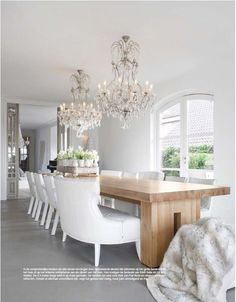 long wooden dining table, white chairs, two large crystal chandeliers  Dining on We Heart It - http://weheartit.com/entry/54341150/via/littlemill