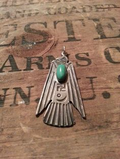 Sterling silver and turquoise thunderbird pendant,  with stamped whirling log.
