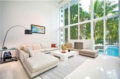 Glassy contemporary mansion in South Florida has glossy white floors, a white sectional couch, arched floor lamp, white coffee table, gray textured rug, high ceilings and a wall of glass overlooking the pool.