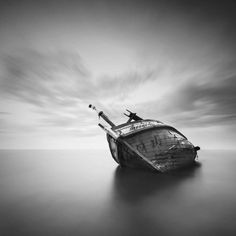 A black and white photo of a ship lying on its side. A photo by Baay Jal.