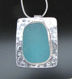 "This bold and rich aqua blue sea glass is just over an inch in length, and carefully bezel set in sterling silver. We have then soldered it onto a hammered sterling silver backing, giving it both texture and interest.  Together it makes for a beautiful and unique statement necklace that will be noticed! It hangs securely on a 20"" sterling silver chain.  Your necklace will arrive gift boxed, and on a card telling the short story of sea glass, as well as the name of the ocean from where it was…"
