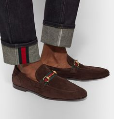GUCCI | Horsebit Suede Loafers The sleek silhouette and timeless appeal of these Gucci loafers make them a favourite among discerning gents. Meticulously crafted in Italy from suede, they're finished with the house's signature striped webbing and horsebit hardware. The rich dark-brown shade will look especially smart with navy suiting. Shown here with Gucci jeans, Gucci cardigan, Gucci shirt.