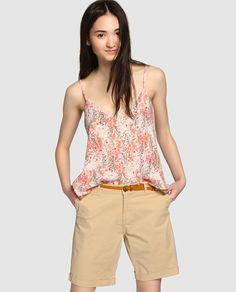 Bermuda en color beige, con cierre de cremallera y botón. Tiene cinturón trenzado a contraste y detalle interior en estampado de flores.