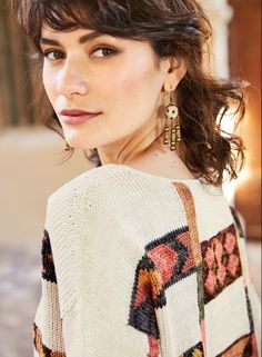 The intriguing pima art knit showcases motifs from a Bhutanese textile in tweeded hues of dusty rose, gold, fern and orange on an oatmeal ground. Intarsia handknit, the fit is relaxed and boxy, with a bateau neck, drop shoulders, side slits and handcrocheted trim. #springsweater #springstyle #springfashion #sweater #lightweightsweater #peruvianconnection #handknit #handknitsweater #artknit #globalyinspired