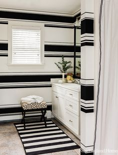 The guest bath takes a dramatic turn with horizontal wallpaper and a black-and-white striped rug.