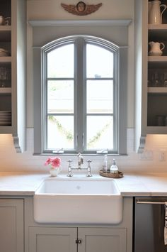 love the farmhouse sink...nice and deep.  love the over hang. Kitchen:   Sally Wheat Interiors - Gorgeous gray kitchen design with gray kitchen cabinets with ...//my dream sink