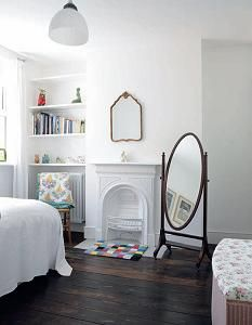 The spare bedroom  has an original Victorian  fireplace and oiled wooden  floorboards.