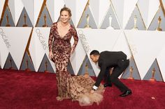 In Honor of Awards Season, 48 Times Celebrities Really Struggled with Their Fancy Clothes It's not easy dressing in couture all the time. Even our favorite celebrities have had outfit mishaps or wardrobe malfunctions. Here, we rounded up some hilarious photos of celebrities struggling with their runway-worthy ensembles—while still looking fabulous!  THE CUTEST COUPLE!! John Legend helps Chrissy Teigen with her dress on the red carpet.
