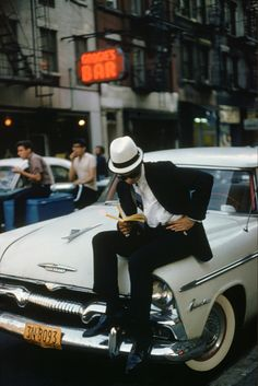"""""""A man sitting on a Plymouth car and reading a book in New York City, 1962. Photo and copyright by Ernst Haas. """""""