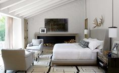 A landscape fireplace, antlers above bed, wide window to the outdoors