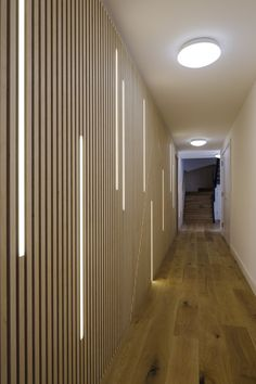 LED lighting dissecting a wall of plywood strips in corridor at Wilberforce Road