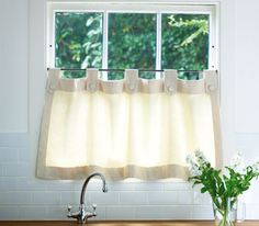 Short curtain hanging from rail on lower part of kitchen window
