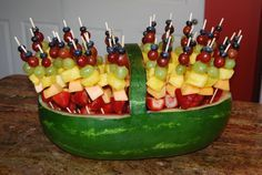 Fruit kabobs in a watermelon basket.