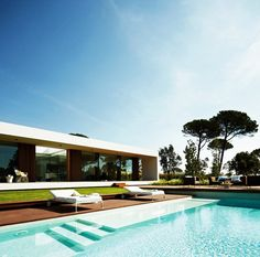 Architecture, Fantastic White Lounge Chairs And Wooden Deck In The Villa Indigo Back Space With Blue Infinity Pool: Amazing Modern House Design Ideas With Wooden Floor