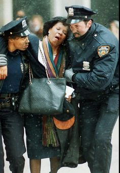 NYPD officers helping a woman on 9/11/2001