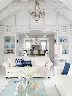 Gorgeous beachy coastal inspired living room decor with whitewashed walls, white sofas and blue and turquoise decor accents