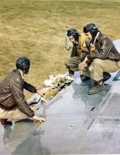 Back at their base, crew members of the Boeing B-17 Flying Fortress heavy bomber, nicknamed 'Sugar-Jo,' sit on the plane's wing and examine damage incurred while on a mission, England, December 6, 1944. (Photo by PhotoQuest/Getty Images)