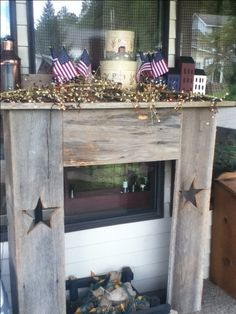 Faux fireplace on the front porch decorated in Americana items--pip berries, tiny lights, flower pots filled with pea gravel and small flags, stacking boxes and saltbox houses from 2x4's. Decorate seasonally for year round displays.