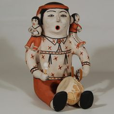 #adobegallery - Cochiti Pueblo Male Storyteller - Drummer Figurine by Seferina Ortiz (1931-2007) - In this figurine, Seferina Ortiz presents a male storyteller with two children perched on his shoulders and concurrently presents him as a Cochiti drummer.  The male is dressed in a fancy ribbon shirt wearing a bola tie and has a red headband.