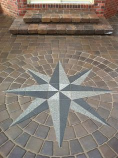 This project design consisted of a patio walk and 2 steps to replace the old worn out concrete pad that was existing. The patio created a nice sized entertaining area perfect for the clients needs. The custom inlaid compass rose was a great idea in the beginning and ended up being a beautiful, custom touch for this project.  Decks and patios