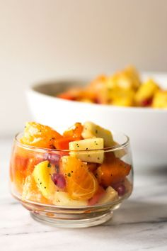 A winter fruit salad made with pineapple, persimmon, citrus and pomegranate) topped with a honey ginger dressing #fruit #salad #persimmon @mjskitchen