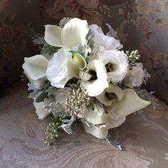 Bridal bouquet with calla lilies, lisianthus, dusty miller, and eucalyptus seeds