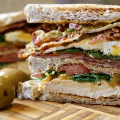 World's best sandwich piled high with grilled chicken, chorizo, ham, fried egg, bacon, cheese, tomato, rocket on a toasted wheat bread.