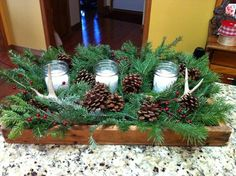 Antlers in wood bowl or tray with greenery and mason jar candles.